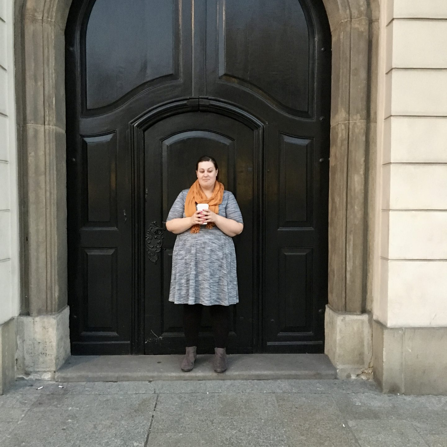 Natasha Theodora standing in front of a large brown door holding coffee